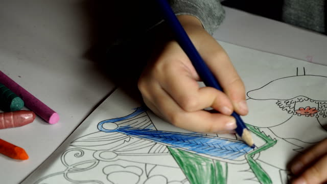 child paints coloring with crayons