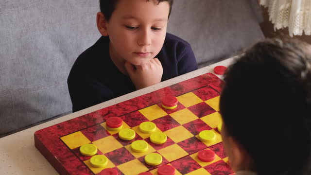 child playing checkers game with his mother - draughts stock videos & royalty-free footage
