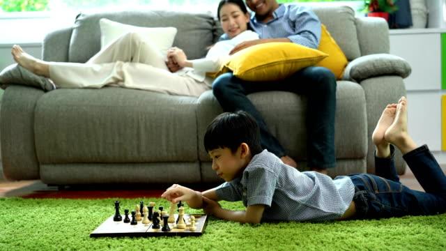 stockvideo's en b-roll-footage met 4k kind spelen schaken terwijl glimlachende ouder kijken naar hem op de bank in een woonkamer thuis - spelletjesavond