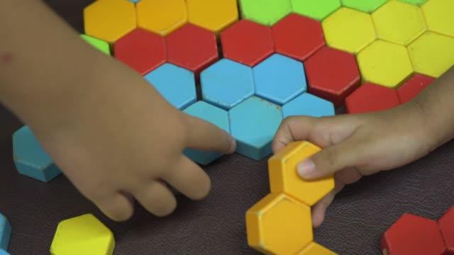 vídeos y material grabado en eventos de stock de niño jugando rompecabezas de colores bloque de madera - mosaico