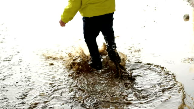 child playing in muddy puddle - footwear stock videos & royalty-free footage