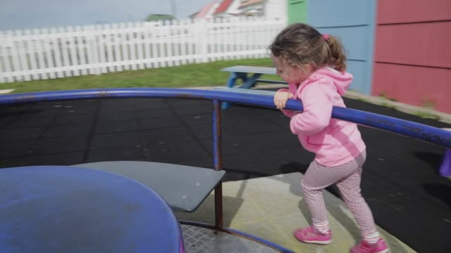 child playing on a playground roundabout - tracking shot stock videos & royalty-free footage