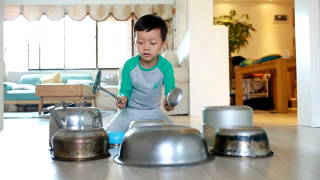 鍋やフライパンが付いている床で遊ぶ子供 - 胡坐点の映像素材/bロール