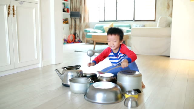 child playing on floor with pots and pans - child sitting cross legged stock videos & royalty-free footage