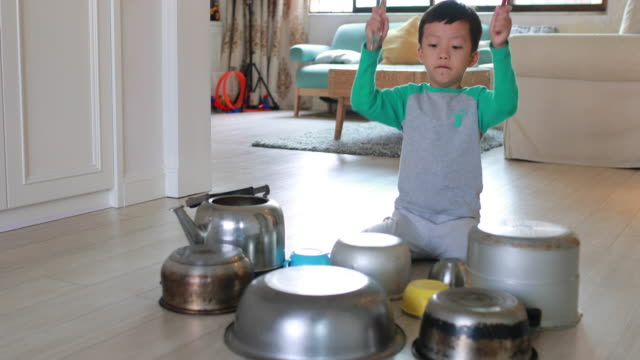 vídeos de stock e filmes b-roll de child playing on floor with pots and pans - criança de escola primária