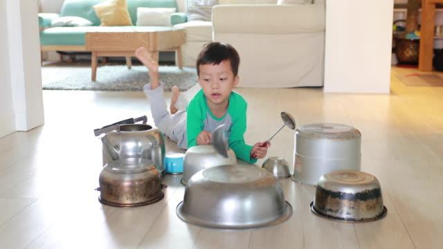 vidéos et rushes de enfant jouant sur le plancher avec des pots et des casseroles - seulement des enfants