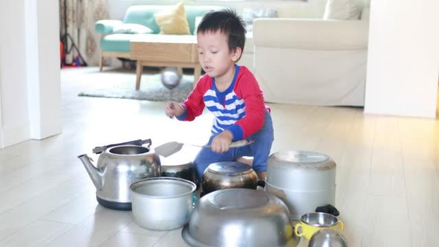 Kind spielt auf Boden mit Töpfen und Pfannen