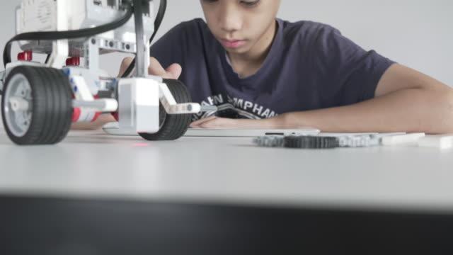 Kind spielt auf selbstgebauten Roboter STEM