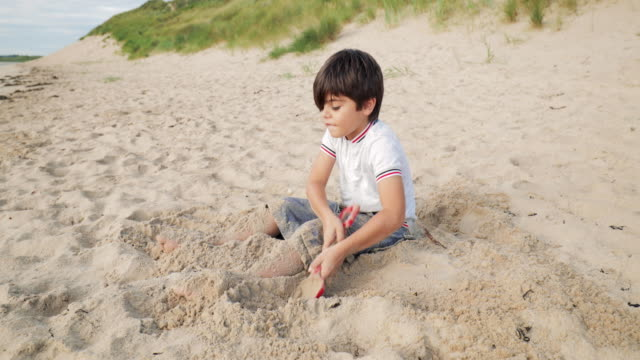 Child Playing On The Beach In The Sand