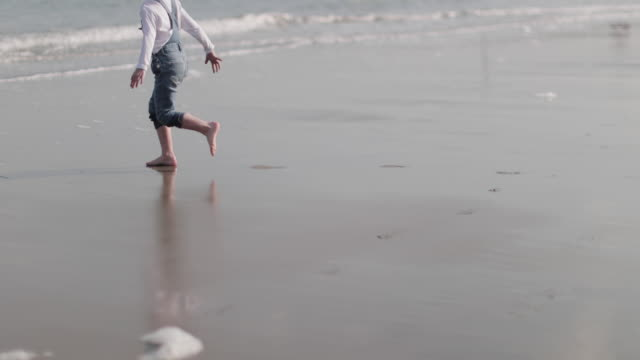 child playing on the beach - primary age child stock videos & royalty-free footage