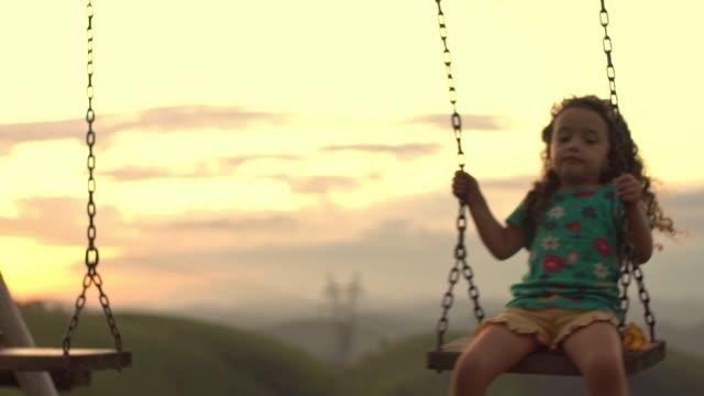 vidéos et rushes de enfant jouant sur la oscillation dans le rétroéclairage - balançoire