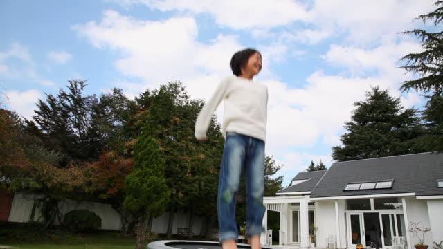 vidéos et rushes de ms child playing trampoline / fujikawaguchiko, yamanashi, japan - bras en l'air