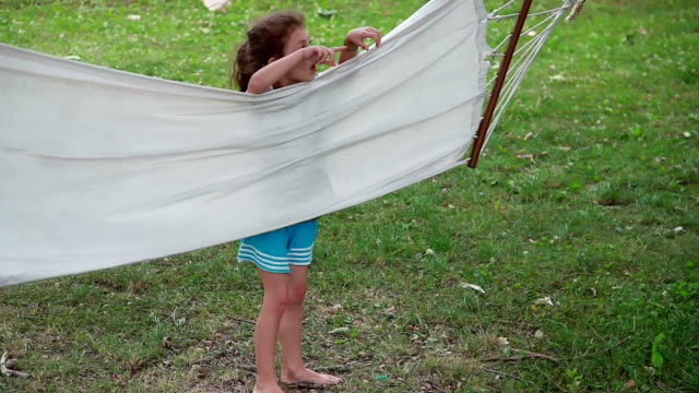 vídeos de stock e filmes b-roll de child playing with a hammock in the backyard - inclinar se pose