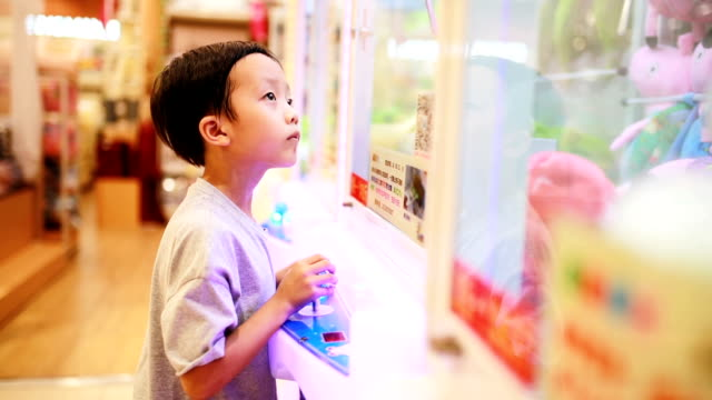 Child playing with a joystick and button on a crane game machine