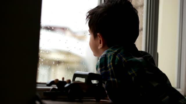 stockvideo's en b-roll-footage met kind spelen met een speelgoedauto door raam - midden oosterse etniciteit