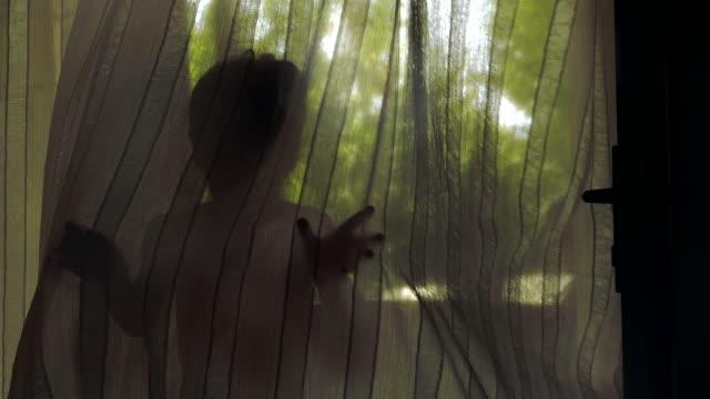 vídeos y material grabado en eventos de stock de niño jugando con la cortina ondulante en el viento. - arte decorativo