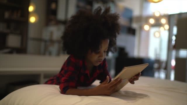 vídeos de stock, filmes e b-roll de criança que joga com tabuleta digital em casa - utilizar o tablet