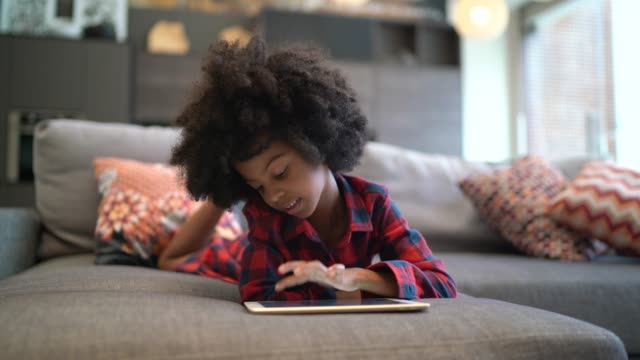 child playing with digital tablet at home - black hair stock videos & royalty-free footage