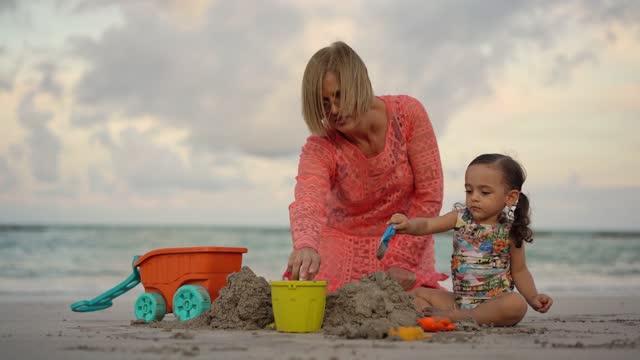 vidéos et rushes de enfant jouant avec la grand-mère sur le sable de plage - 2 3 ans