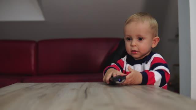 リモコンで遊ぶ子供 - テレビのリモコン点の映像素材/bロール