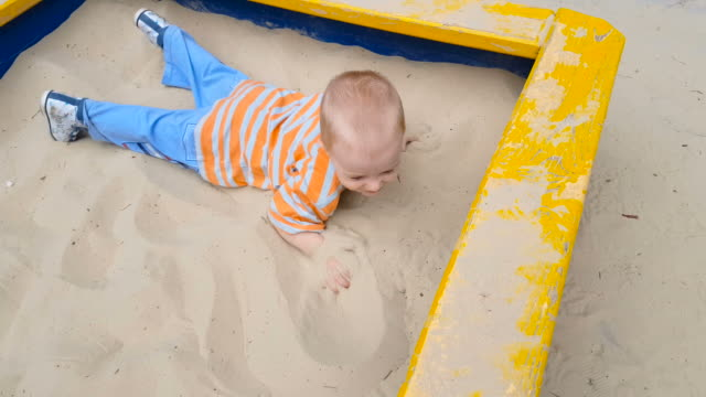 child playing with sand crawling in the sandbox - sand pit stock videos and b-roll footage