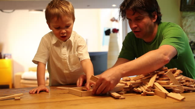 child playing with toy blocks with his father - primary age child stock videos and b-roll footage