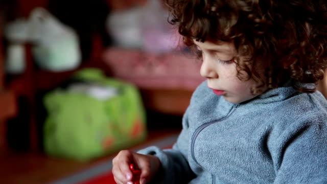 Kind spielt mit Spielzeug im Schlafzimmer