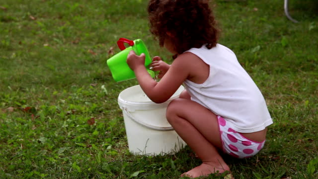 Child playing with water in the bucket