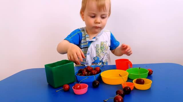vídeos de stock, filmes e b-roll de uma criança joga com cerejas e pratos - só bebês meninos