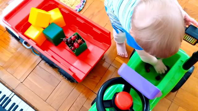 vídeos de stock, filmes e b-roll de uma criança joga com cerejas e brinquedos - só bebês meninos