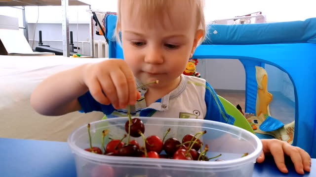 A child plays with cherries