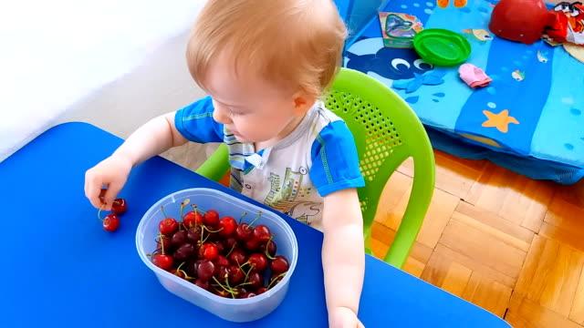 vídeos de stock, filmes e b-roll de uma criança joga com cerejas - só bebês meninos