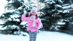 A child plays with snowballs.