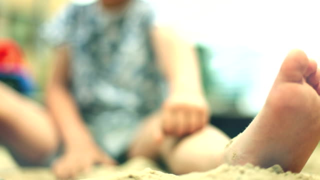 Child poured sand on the feet in sandpit