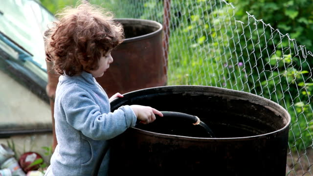 child pouring water from hose to the big metal cask - standing water mosquito stock videos & royalty-free footage