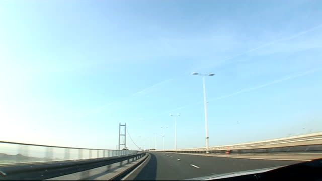 scenes from hull england yorkshire hull point of view from car as along dual carriageway and passing over the humber bridge / sun shining on the... - キングストンアポンハル点の映像素材/bロール