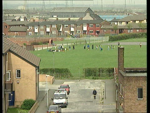 Child poverty report published ENGLAND TBV Woman walking along past derelcit flats on housing estate PULL OUT TGV Children on playing field near...