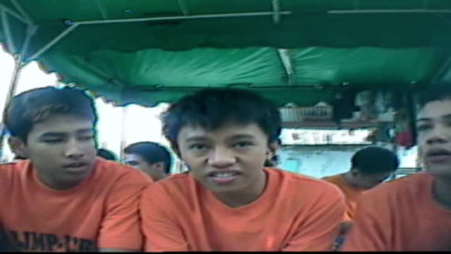 child prisoners kept in appalling conditions rogers handing over video camera to prison guard boy prisoners wearing orange tshirts walking along boy... - prisoner orange stock videos & royalty-free footage