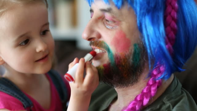 child putting lipstick and makeup on father - daughter stock-videos und b-roll-filmmaterial