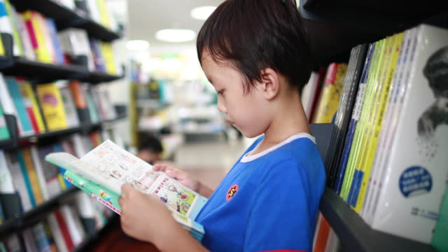 child reading a book in the library - elementary age stock videos & royalty-free footage