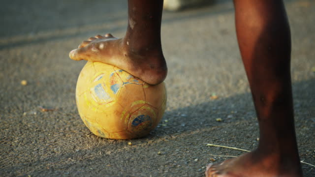 Child rests foot on soccer ball, close up