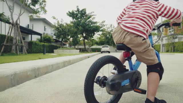 vidéos et rushes de enfant conduisant un vélo d'équilibre sur la rue. - selle