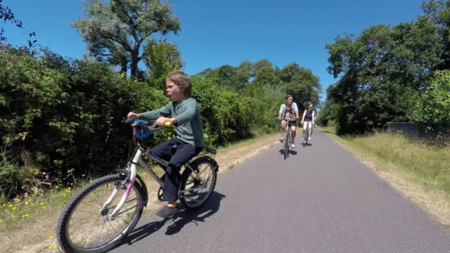 child riding a bike with two women - famiglia con due figli video stock e b–roll