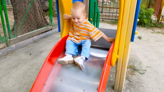 vídeos de stock, filmes e b-roll de criança andando em um slide no playground - só bebês meninos