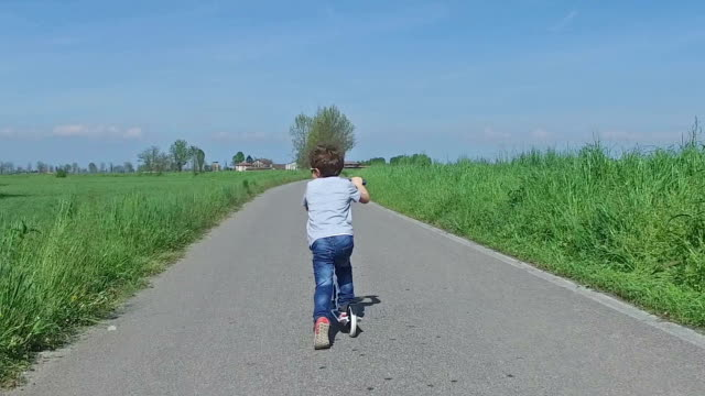 Child riding scooter on country road