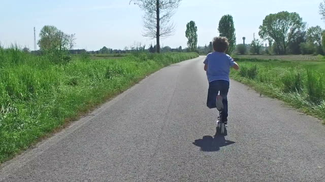 stockvideo's en b-roll-footage met kind paardrijden scooter op landweg - pjphoto69