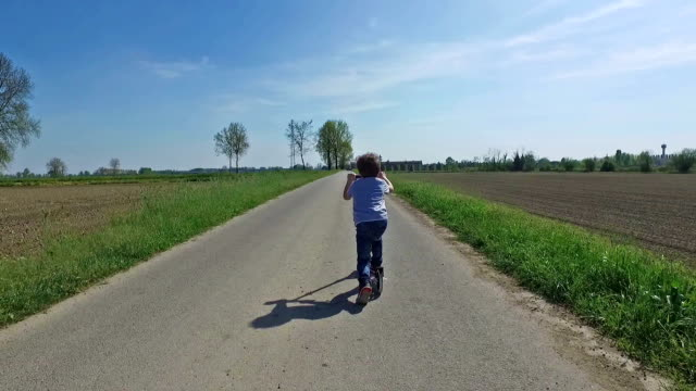 child riding scooter on country road - push scooter stock videos and b-roll footage