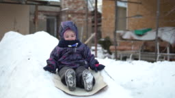 A child rolls on a snow slide. Winter fun on the street. In the cold winter, the child is dressed in a jacket with a scarf. Slow motion
