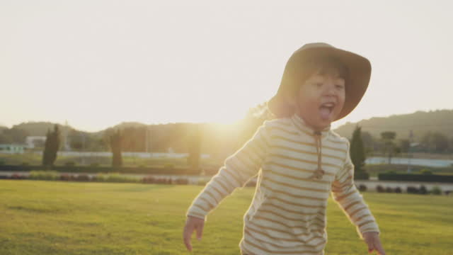 child run in field with sunset - innocence stock videos & royalty-free footage