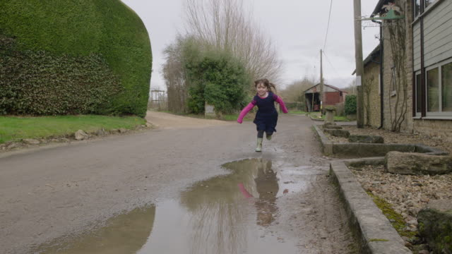 vídeos de stock e filmes b-roll de a child running through puddle - barro